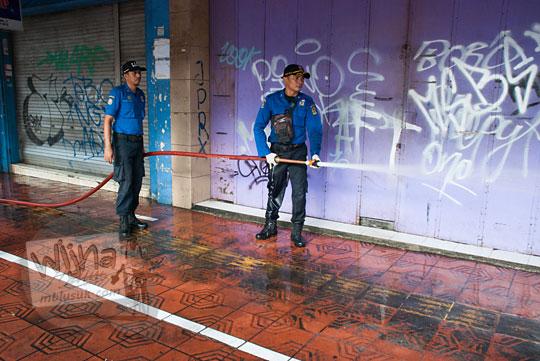 petugas pemadam kebakaran jogja menyemprot area kios suvenir cenderamata trotoar pejalan kaki saat acara bersih-bersih malioboro pada selasa wage