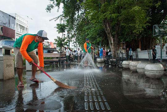 petugas satgas kebersihan kota yogyakarta menyapu trotoar area pedestrian baru di depan hotel inna garuda dengan sapu lidi saat acara bersih-bersih malioboro pada selasa wage
