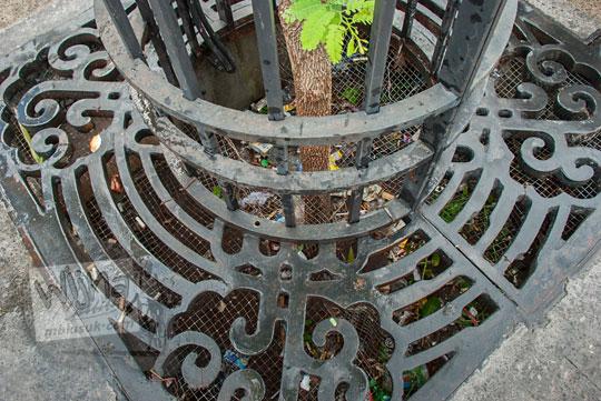foto tumpukan sampah bungkus plastik botol air mineral di dalam lubang pohon kawasan pedestrian malioboro tidak bisa diambil sebelum kerangkeng besinya dibongkar