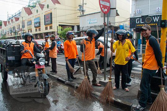 foto mas-mas bapak-bapak satgas kebersihan kota yogyakarta berseragam oranye sedang ngumpul ngobrol di sela-sela kegiatan reresik malioboro rutin setiap selasa wage