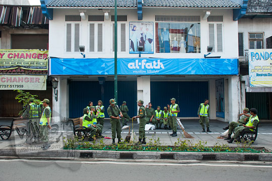 foto bapak-bapak dan ibu-ibu linmas kota yogyakarta sedang duduk mengobrol di depan toko busana muslim al-fath saat acara reresik malioboro rutin setiap selasa wage