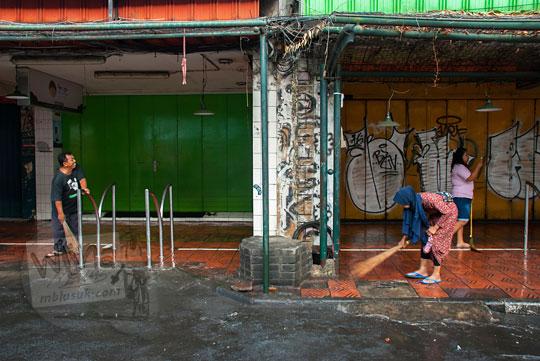 pasangan bapak dan ibu pemilik kios cenderamata suvenir yang biasa berjualan kaos murah di malioboro yogyakarta sedang menyapu trotoar saat acara bersih-bersih selasa wage