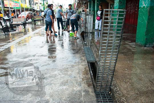 tutup saluran selokan pembuangan air di area pedestrian malioboro sisi timur diangkat untuk dibersihkan oleh bapak-bapak dari paguyuban warung lesehan dan angkringan