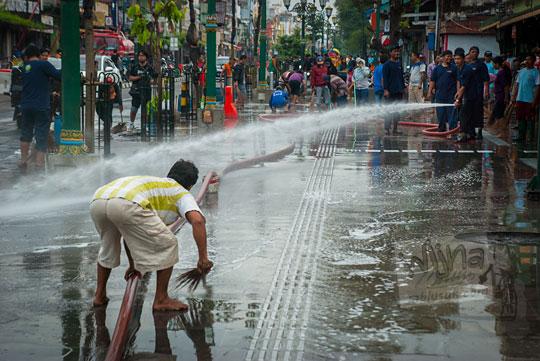 trotoar area pedestrian di depan pintu barat pasar beringharjo disemprot air oleh petugas pemadam kebakaran kemudian disapu bersih oleh seorang bapak pedagang kaki lima pada kegiatan reresik malioboro rutin setiap selasa wage
