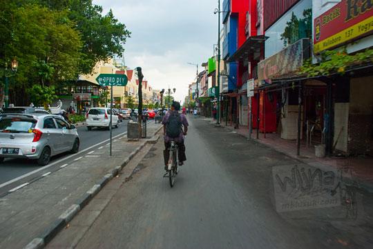 foto seorang bapak pesepeda lewat jalan malioboro sisi barat yang sepi pada selasa wage