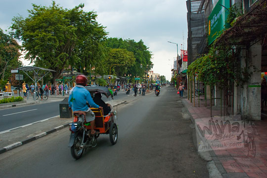 foto pengendara becak motor lewat jalan malioboro sisi barat yang sepi pada selasa wage