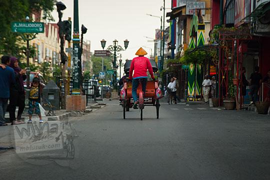 foto becak dipotret dari belakang lewat jalan malioboro sisi barat yang sepi pada selasa wage