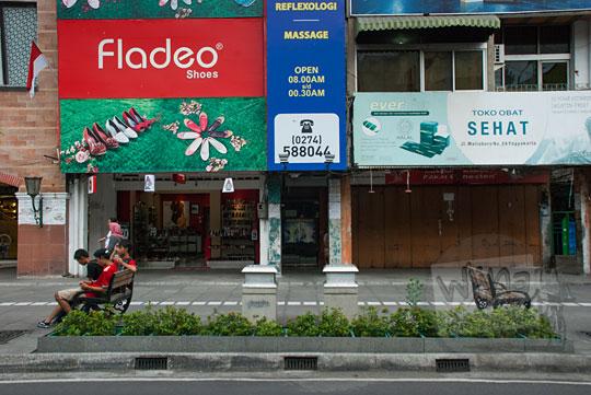 trotoar area pejalan kaki pedestrian malioboro di sekitar hotel mutiara tempat jualan lumpia enak murah terlihat sepi dari kios pedagang kaki lima pada selasa wage