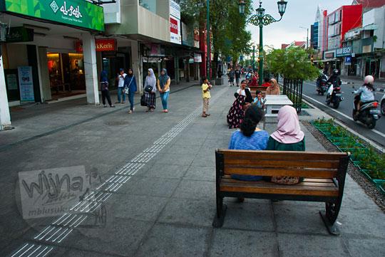 cewek jilbab duduk berduaan sambil pelukan dilihatin orang-orang yang lewat di bangku kayu area pedestrian malioboro