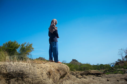 cewek jilbab pakai celana panjang berdiri di tanah gersang dengan langit biru