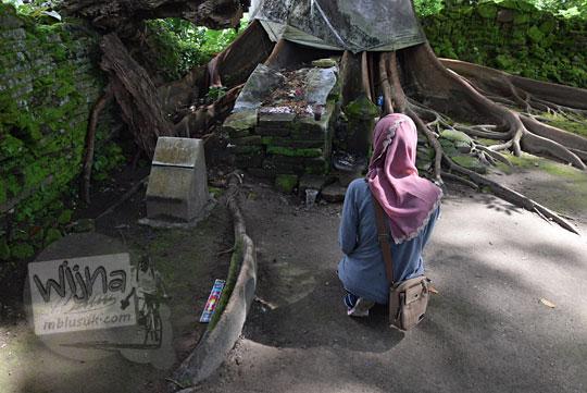 seorang peziarah wanita berhijab sedang berdoa di depan makam dalang ki panjang mas di pemakaman gunung kelir pleret