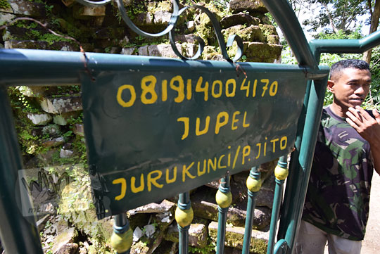 papan kayu bertuliskan nomor telepon pak jito sang juru pelihara makam gunung kelir yang terpajang di gerbang masuk