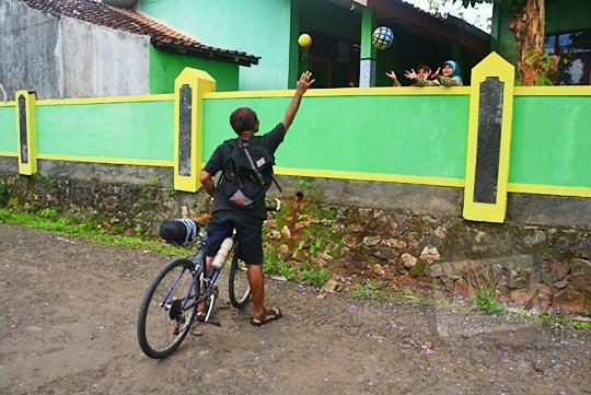 pria naik sepeda sedang melempar bola ke anak sd di balik pagar sekolah