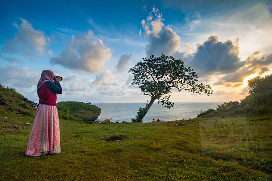 foto cewek berjilbab motret pohon yang tumbuh di pinggir tebing pantai kesirat gunungkidul yogyakarta pada zaman dulu agustus 2018