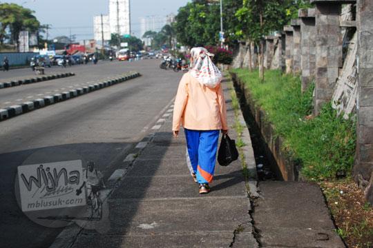 wanita berjalan kaki di trotoar kampus unpad jatinangor
