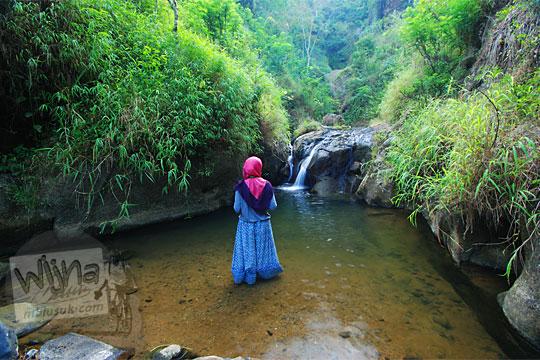 perempuan memakai rok dan jilbab sedang bergaya di sungai nabak desa loano