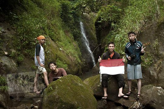 empat orang pria berfoto di curug klanceng putih loano sambil membawa bendera merah putih indonesia