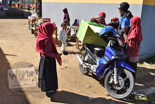 anak perempuan kecil siswi berjilbab sedang membeli jajan di mas pedagang jajanan pakai sepeda motor di sd negeri sembungan kejajar wonosobo pada zaman dulu Agustus 2016