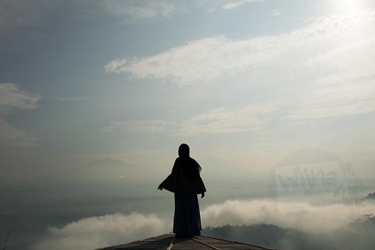 cewek memakai jilbab berfoto siluet di panggung bambu punthuk sukmojoyo borobudur
