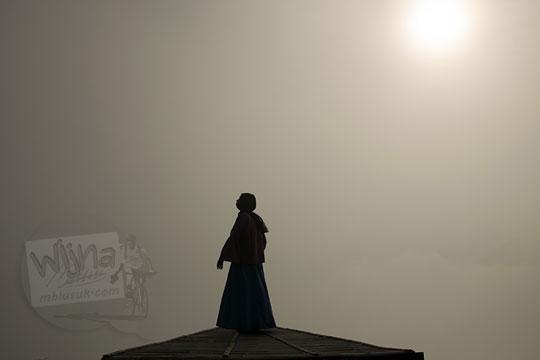 cewek memakai jilbab berfoto siluet kabut di punthuk sukmojoyo borobudur