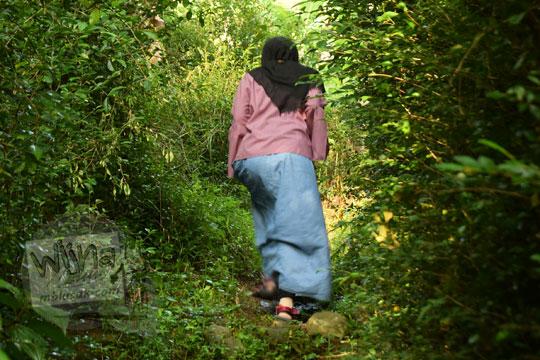 cewek memakai jilbab berjalan kaki melewati semak dan hutan