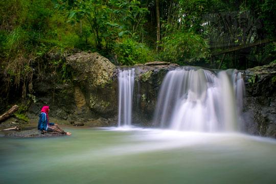 cewek duduk di dekat air terjun rahasia yang indah di desa kemejing loano purworejo