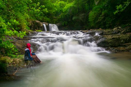 cewek duduk di pinggir sungai dekat air terjun yang masih sepi di desa kemejing loano purworejo