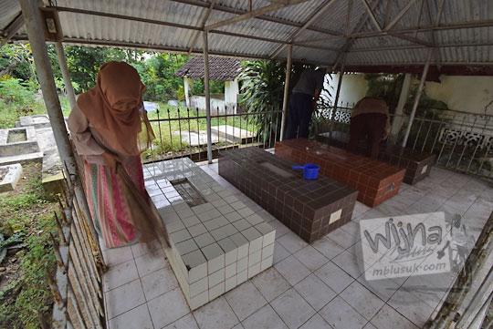 foto wanita berjilbab sedang menyapu membersihkan makam dalam rangka tradisi ruwahan di klaten jawa tengah