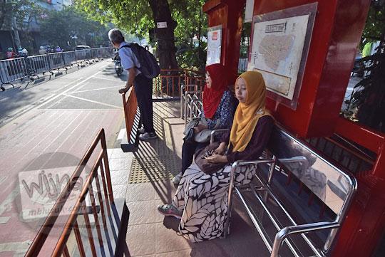 foto penumpang di halte batik solo trans seberang stasiun purwosari sedang menunggu kedatangan bus