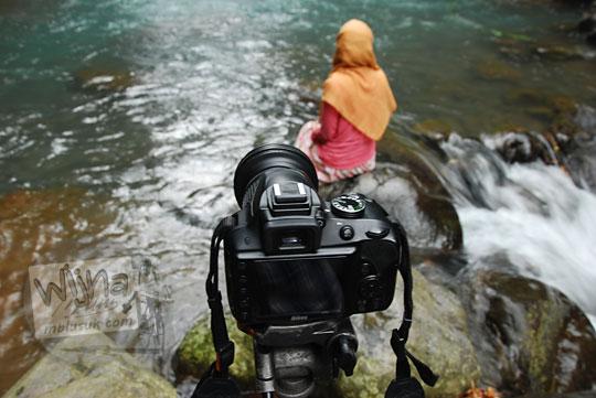 seorang perempuan memakai jilbab duduk di sungai membelakangi kamera dslr