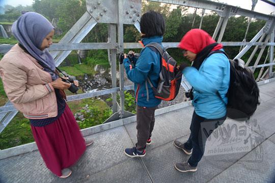tiga fotografer cewek sedang memotret dari atas jembatan mangunsuko di kecamatan dukun kabupaten magelang jawa tengah