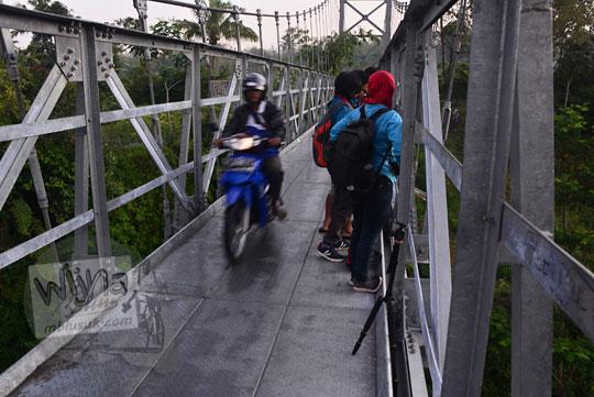 warga naik sepeda motor melintas samping fotografer yang sedang memotret dari atas jembatan mangunsuko kecamatan dukun kabupaten magelang jawa tengah