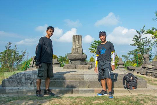 dua orang pria berfoto bersama lingga raksasa di kompleks candi sari boyolali pada zaman dulu Agustus 2017
