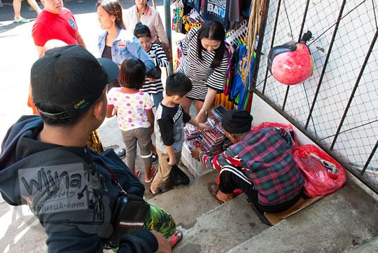 foto wisatawan membeli stroberi di pasar songgoriti kota batu pada April 2017