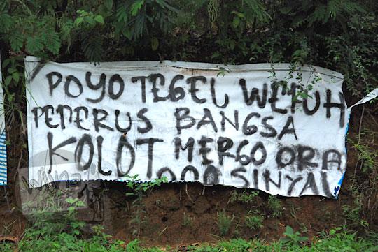 spanduk susah sinyal poyo tegel kolot di tepi jalan raya desa purwosari girimulyo kulon progo yogyakarta pada desember 2018