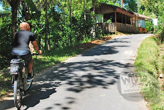 foto pria botak bersepeda nanjak lewat jalan suroloyo