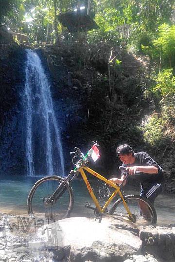 foto cowok menyuci sepeda di curug watu jengger samigaluh kulon progo yogyakarta