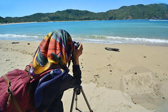 perempuan berjilbab sedang memotret pantai di lombok