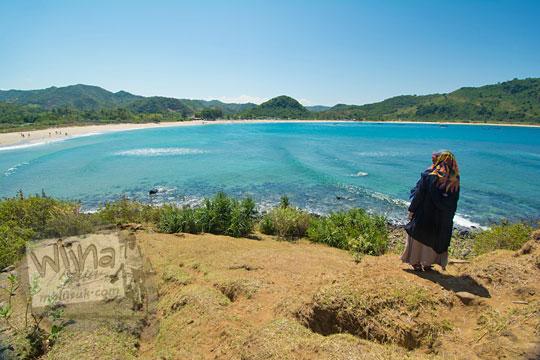perempuan berdiri di puncak tebing pantai mawun lombok