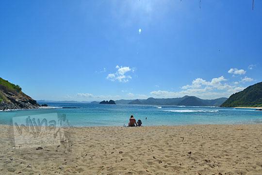 bule perempuan pakai baju renang bikini sedang duduk sendiri di pantai mawi lombok
