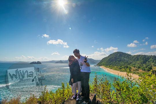 pasangan bulan madu berfoto bersama di pantai mawi lombok