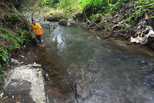 pria jalan kaki menyusuri sungai petilasan keraton gaib bathok bolu di dusun sambiroto purwomartani kalasan tahun 2018