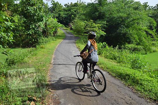 bersepeda di jalan tanjakan menuju situs candi abang, berbah, sleman, yogyakarta pada Januari 2018