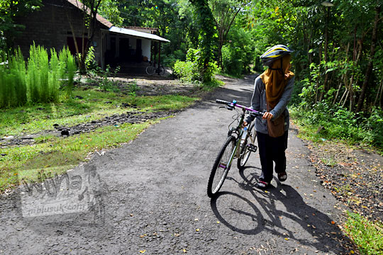 menuntun sepeda di tanjakan ke arah situs candi abang, berbah, sleman, yogyakarta pada Januari 2018