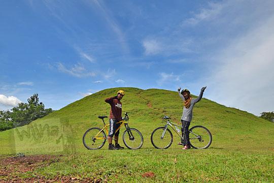 cewek cowok foto dengan sepeda di lapangan situs candi abang, berbah, sleman, yogyakarta pada Januari 2018