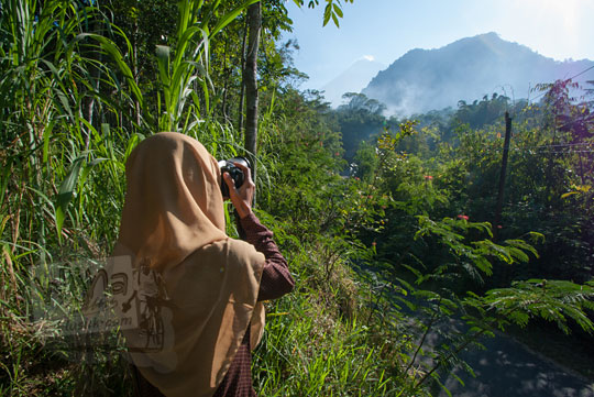 wanita memotret gunung merapi dari turgo