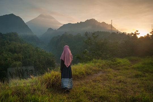 perempuan berjilbab berdiri gunung merapi sleman