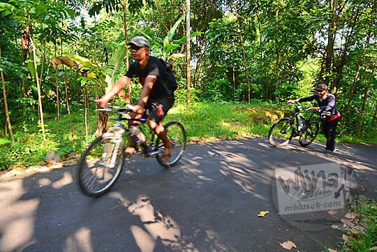 pria cowok bersepeda nanjak ke bukit teletubbies di prambanan sleman yogyakarta