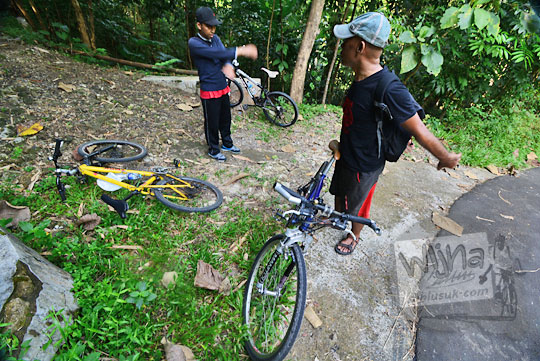 dua pesepeda beristirahat di tengah tanjakan ke bukit teletubbies di prambanan sleman