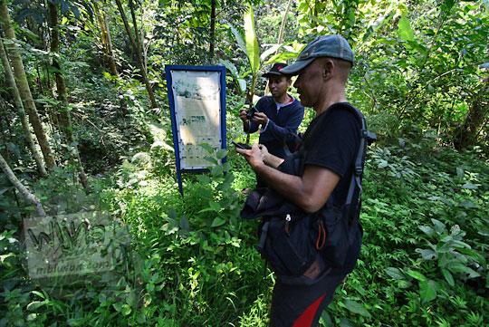 dua orang pria melihat lokasi tanah ambles di dusun nglepen sumberharjo prambanan
